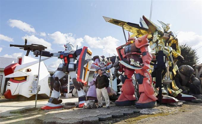 アニメ「機動戦士ガンダム」に登場するモビルスーツの巨大像と制作者の鈴木敏美さん=青森県おいらせ町