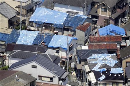 地震で屋根瓦が崩れ、ブルーシートが掛けられた住宅=24日、大阪府高槻市