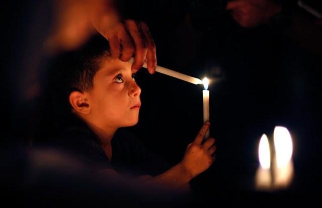 Palestinian boy lights a candle