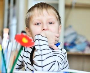 Un bambino mancino tiene la penna nella mano sinistra