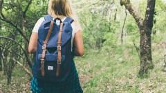 Una ragazza con uno zaino durante un'escursione in un bosco