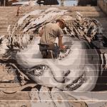 Lo street artist Diavù al lavoro su una scalinata romana
