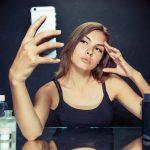 Ragazza, specchio e cellulare