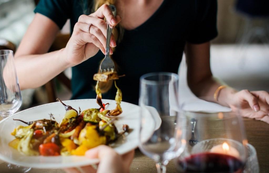 Una donna mangia delle verdure in un piatto al ristorante