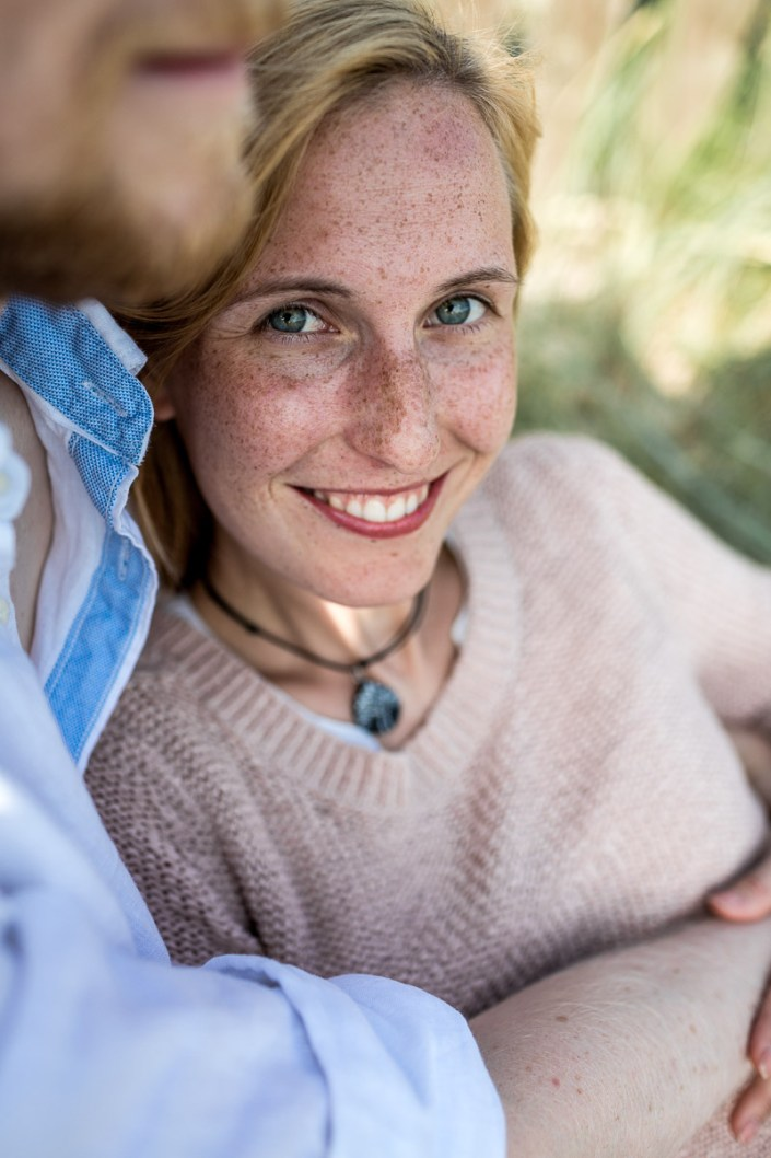 Paar am Strand Umarmung Frau Blick in die Kamera lacht Düne Laboe Paarshooting