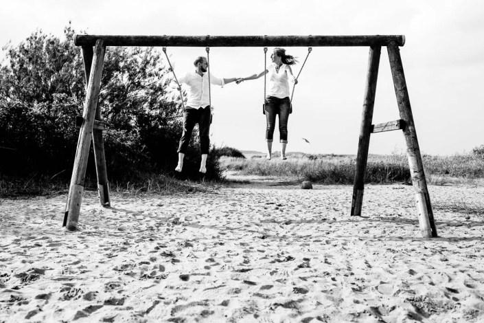 Mann und Frau schaukeln am Strand Düne Laboe Paarshooting