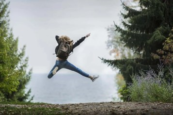 Girl jumping on a mountain path representing the Angel Number 7 being a number to celebrate seeing.