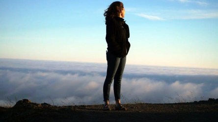 Are you living up to your potential? Woman standing on edge of cliff looking back on the clouds below her representing the message of the angel number 22 telling us we are meant to be more.