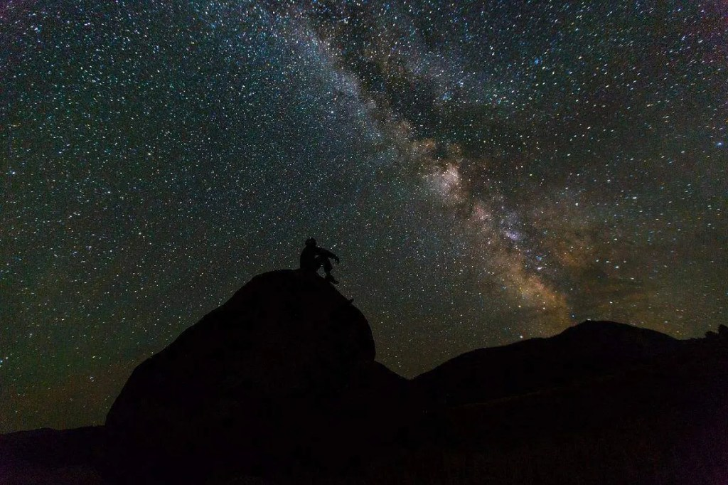 Man sitting under a starry night sky. In order to manifest your intentions make friends with the universe.