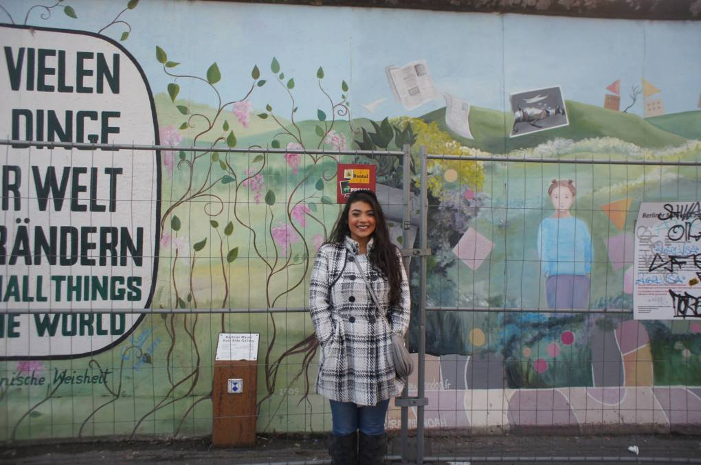 Berlin in 1 Day: girl wearing plaid coat standing in front of an East Side Gallery mural
