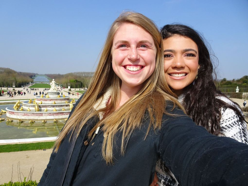 two girls in front of fountain and garden background in Versailles
