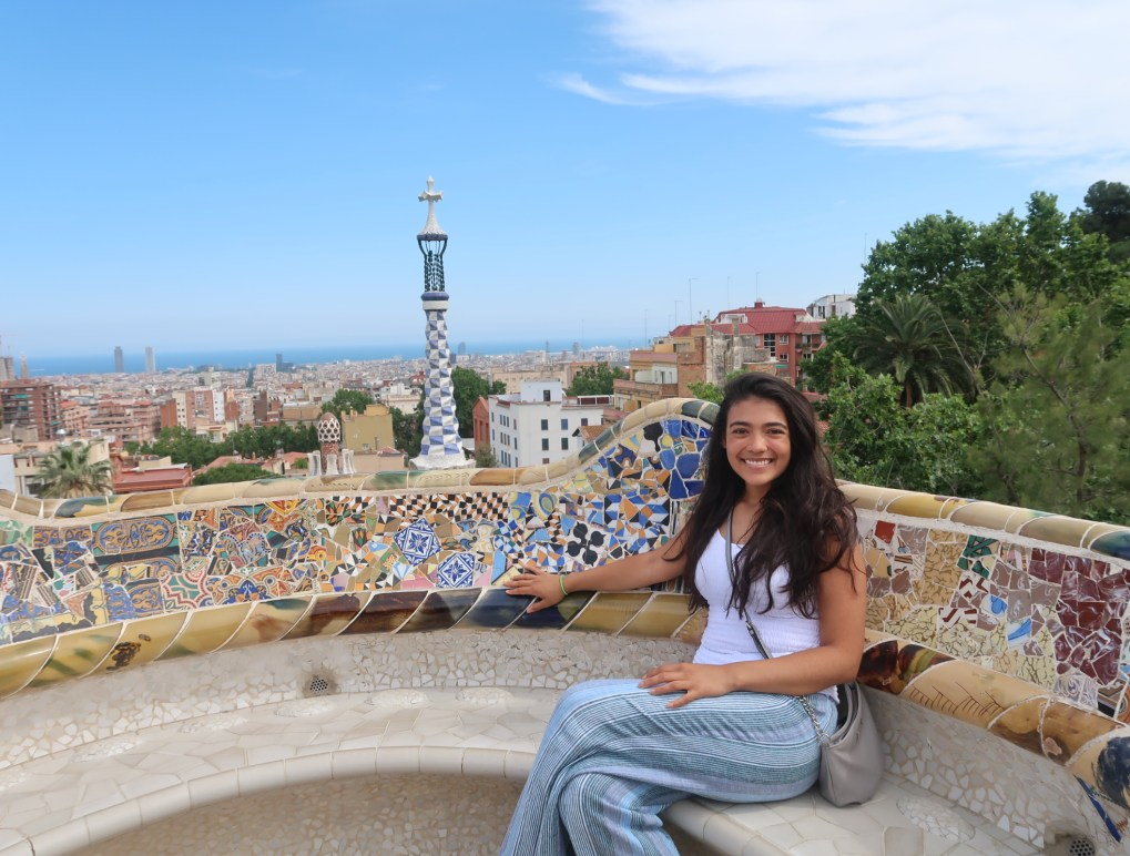 girl wearing white top and blue pants sitting on mosaic bench with city in the distance
