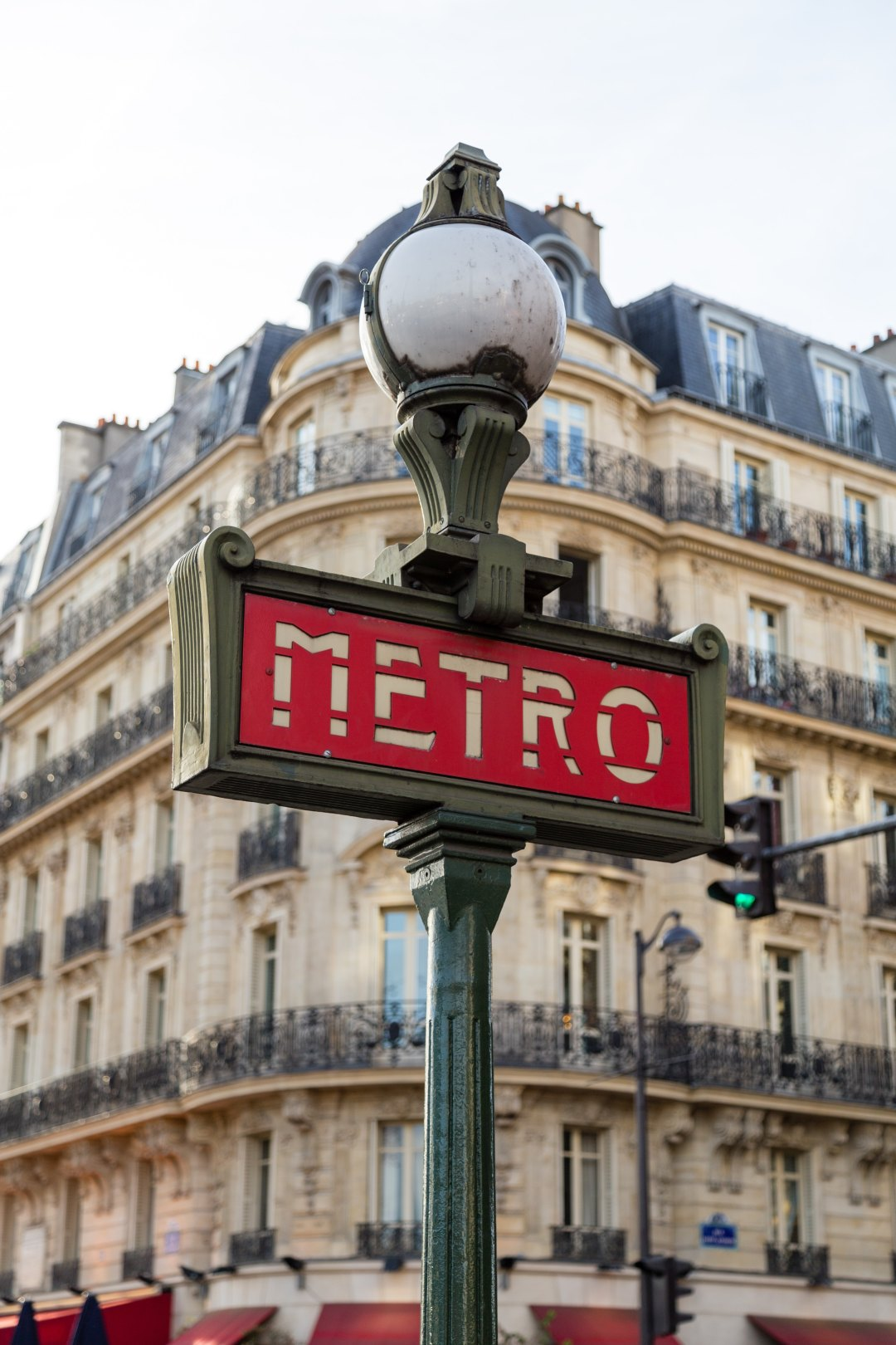 paris metro sign with building and balconies in the background