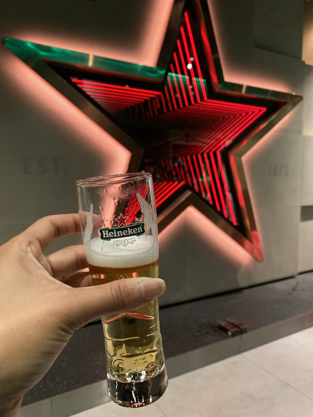 Glass of Heineken in front of red star