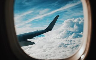 plane window with wing and clouds in background