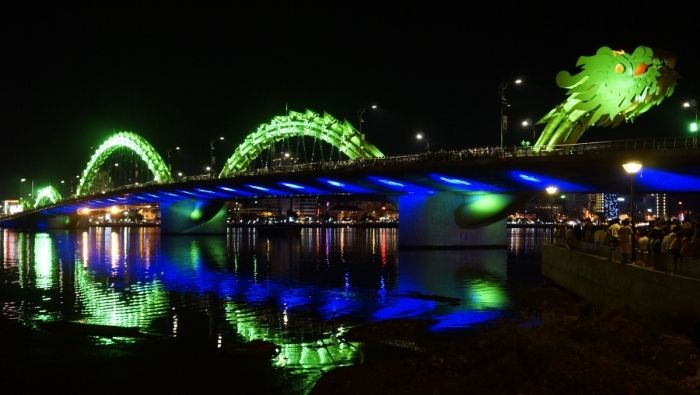 Green dragon bridge lit up at night in Da Nang, Vietnam
