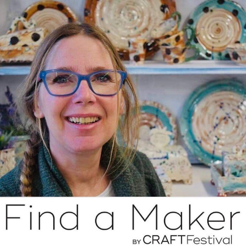sarah monk ceramics portait in front of shelves of her work at eastnor pottery