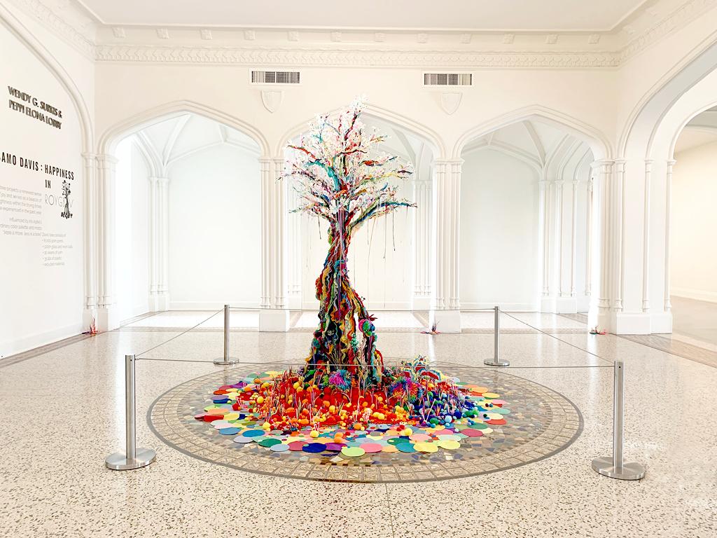 Samo Davis, Happiness in ROYGBIV, 2021, Plastic, pom poms, resin, yarn, clay, recycled materials. Courtesy of the artist. Photo: Sarasota Art Museum