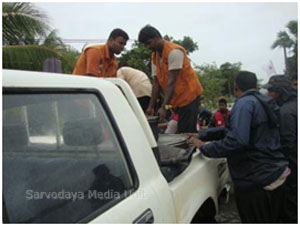 Boiled pigeon pea from Sarvodaya being unloaded at Narippulthoddam School Pickup for distribution to flood victims