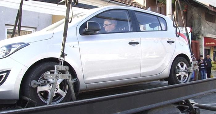 S-a urcat în mașina ridicată de poliție pe trailer (video)