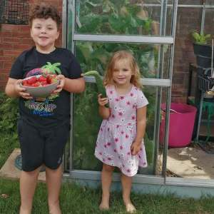 Oscar and Olivia with the Strawberries and  Cucumber that we have grown.