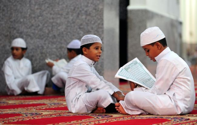 Saudi boys recite verses from the Koran, Islam's holy book, at a mosque in the Red Sea city of Jeddah on August 27, 2009. The rising number of swine flu cases and deaths across the Middle East has cast a cloud over the Muslim fasting month of Ramadan, with a plunge in the number of people going on pilgrimage to Mecca. AFP PHOTO/OMAR SALEM