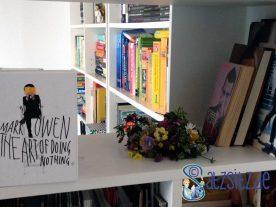 Mark Owen, Robbie Williams und Michael Jackson Bücher neben einem Blumenstrauß im Regal.