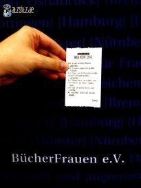 """Jana Stahl hält ihren """"Brain Poetry"""" Zettel vor die blaue Standwand der BücherFrauen"""