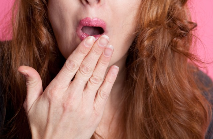 Close Up Of Woman Covering Mouth With Hand