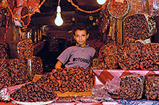 In Sana'a, Yemen, a young vendor sells dates imported from Saudi Arabia. All are sorted and priced by variety and ripeness.