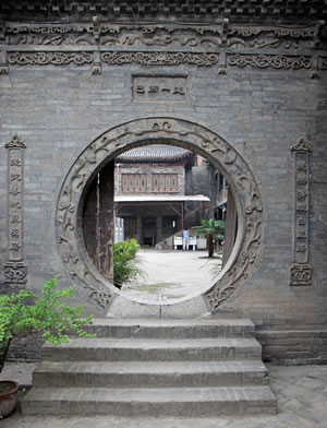 Offering both an entry and a frame for the view beyond it, a circular opening in a wall is known in China as a moon gate. A common feature in gardens, it was also used in religious architecture and, as we see here, in the wall at the Great Mosque of Xian.