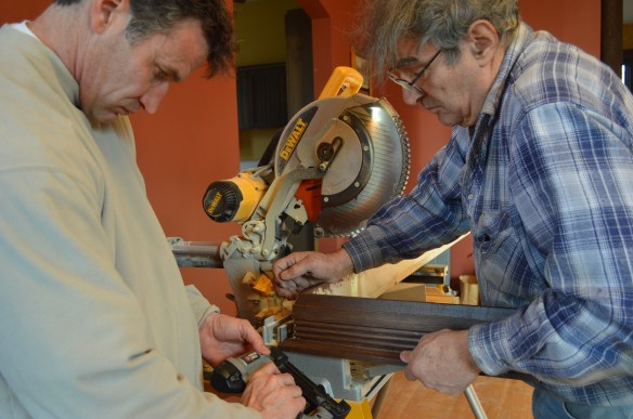 Mark Cardis, left, and Art Kollias work on a piece of crown molding to be used above one of the fireplaces. (photo/Cindy Hadish)