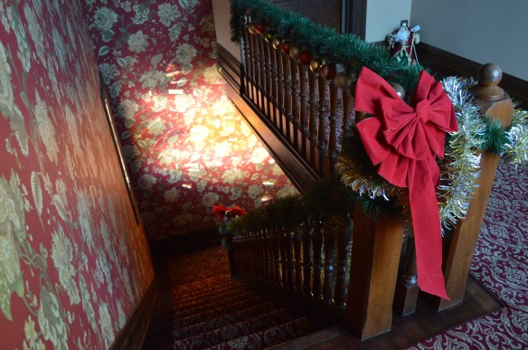 The grand staircase of the Victorian home is decorated for the holidays. (photo/Cindy Hadish)