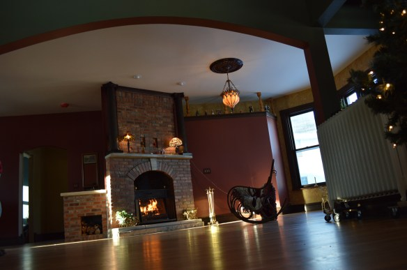 Fire from a rebuilt fireplace reflects on the wood floors of the living room. (photo/Cindy Hadish)
