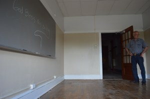 Sanctuary member Richard Hayes, who has been volunteering in the renovation of the former Lincoln Elementary School, shows one of the classrooms, with hardwood floors and an original door, on Wednesday, June 25, in Cedar Rapids, Iowa. (photo/Cindy Hadish)