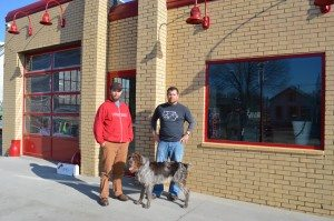 Tony Burnett, left, and Frank Stephen, are shown with Scruffy, one of the shop dogs at Red Ball Printing in New Bohemia. (photo/Cindy Hadish)