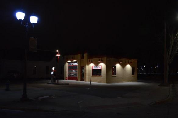 A vintage Skelly gas pump and original light pole are illuminated at night at Red Ball Printing in New Bohemia. (photo/Cindy Hadish)