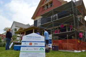 """Volunteers with Habitat for Humanity's """"A Brush with Kindness"""" program begin painting the house earlier this year. (photo/Cindy Hadish)"""
