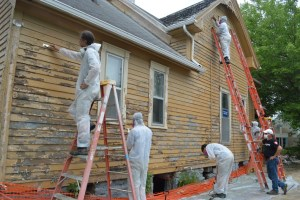 AmeriCorps members work to remove paint from the house earlier this summer as part of a volunteer effort. (photo/Cindy Hadish)