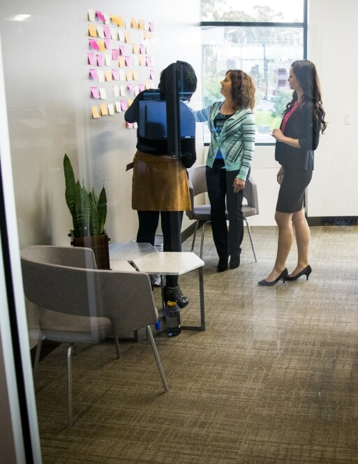 Three people looking at a wall of sticky notes