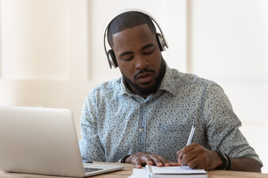 man working on laptop taking notes with a pen