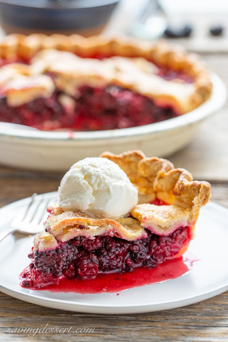 a slice of blackberry pie with a scoop of ice cream