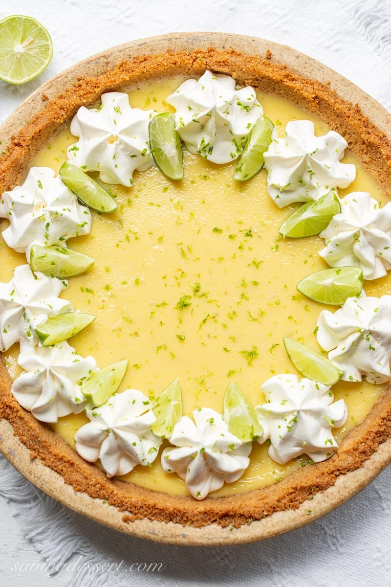 Key Lime Pie with graham cracker crust, garnished with lime zest, key lime wedges and whipped cream