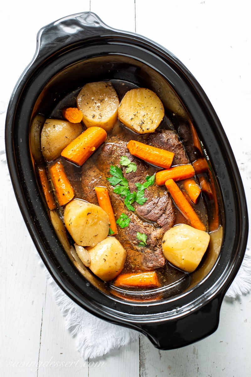 A slow cooker with a pot roast, carrots and potatoes in broth