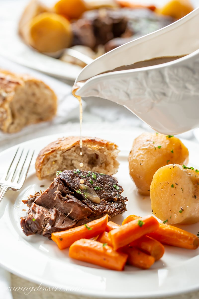 A plate of slow cooker pot roast with carrots, bread and potatoes drizzled with gravy