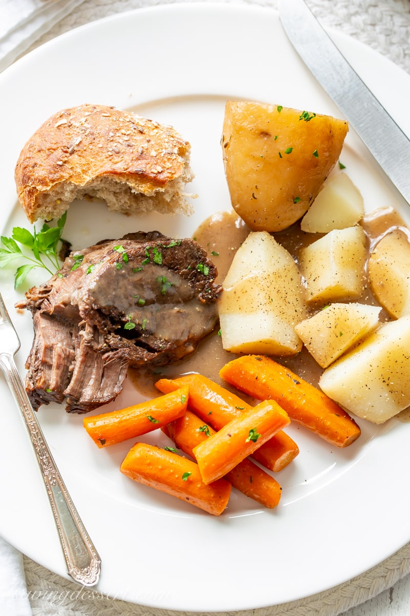 A dinner plate with slow cooker pot roast covered in gravy with roasted potatoes, carrots and crusty bread