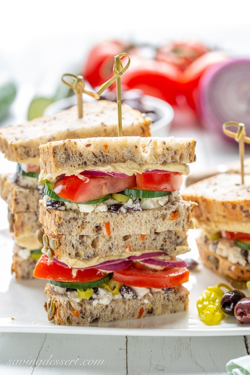 A Greek Salad Hummus Sandwich with tomato, cucumber and red onion