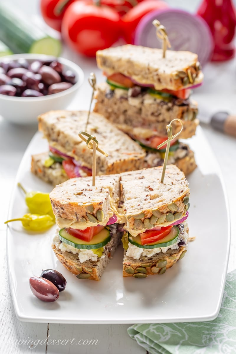 A tray of sliced Greek Salad Hummus Sandwiches served with olives and peppers.
