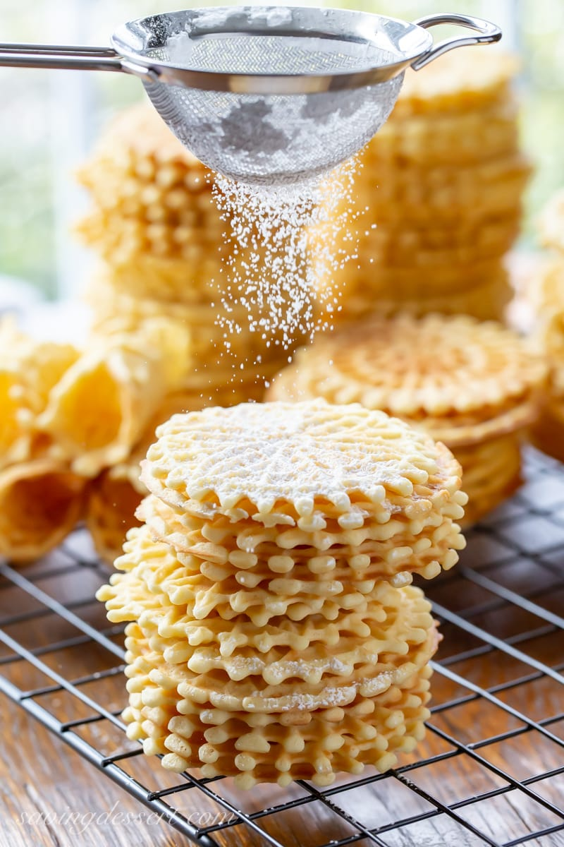 Stacks of classic pizzelle cookies dusted with powdered sugar