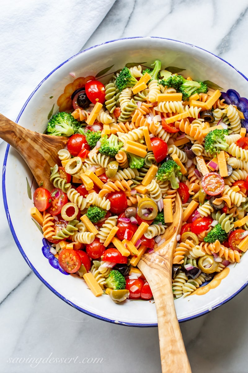 A bowl of pasta salad with cheese, olives, tomatoes, broccoli and spiral noodles tossed in a zesty Italian dressing